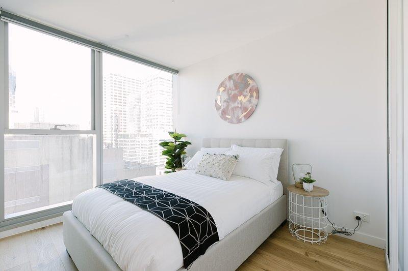 La camera da letto principale con un letto queen size e soffici cuscini.