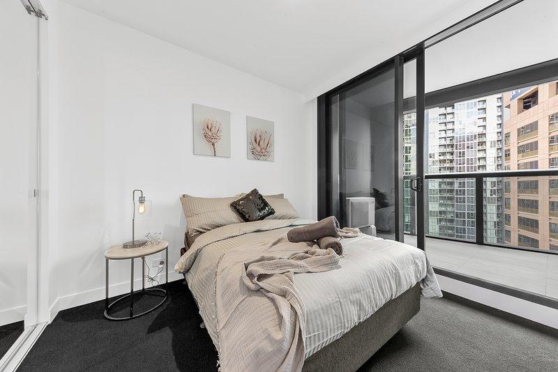 O quarto principal com uma cama queen size e travesseiros de pelúcia.