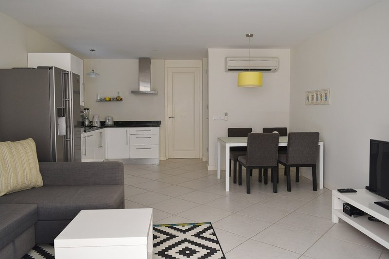 Bright open space for living, dinning and kitchen with aconvenient guest bathroom.