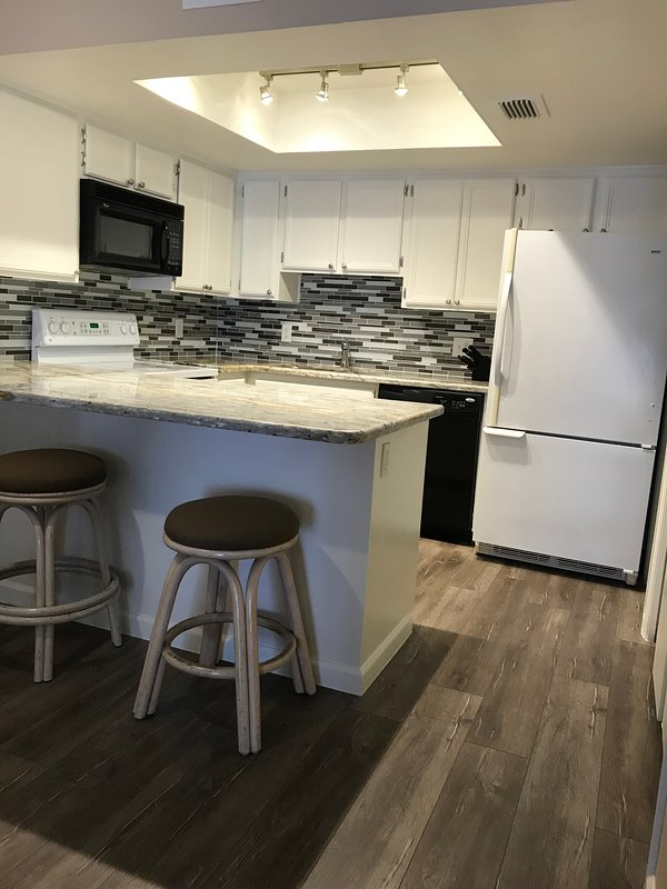 Kitchen with granite countertop, Dishwasher, and large wide Bottom Freezer Refrigerator