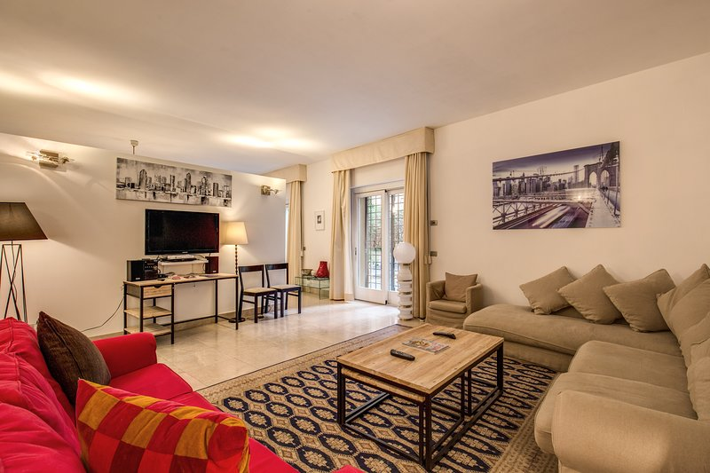 Spacious living room at ground floor with two big sofas, TV and access to shared courtyard