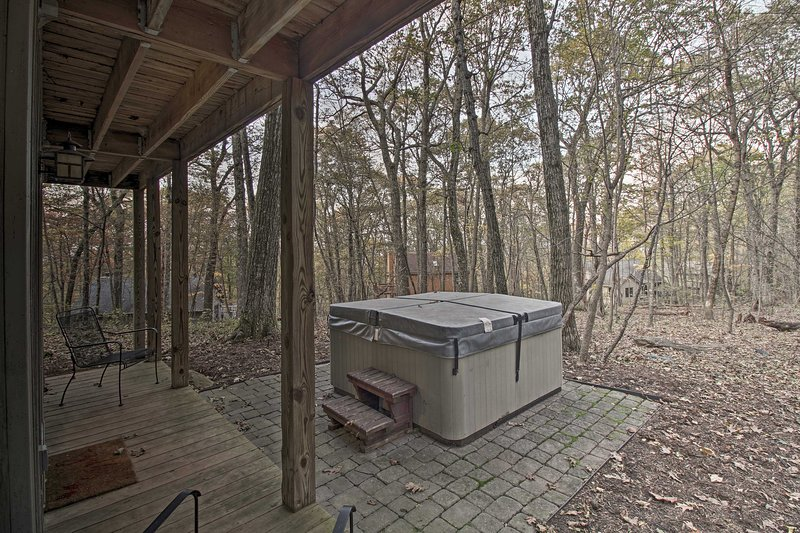 It features a private hot tub with scenic, wooded views.