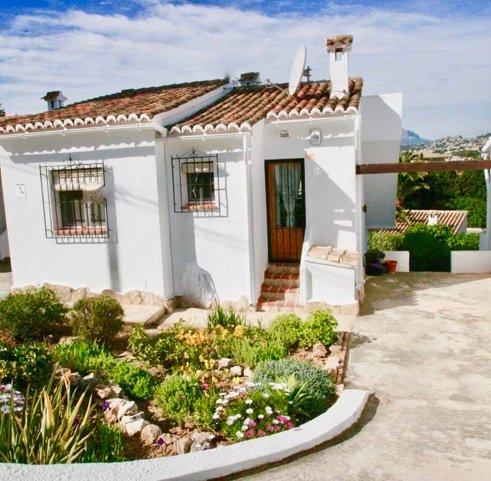 Fachada de la villa con jardín y zona de aparcamiento.