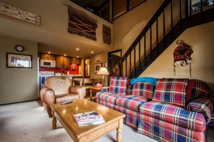 Techos abovedados en una sala de estar abierta con chimenea, HDTV y WiFi.