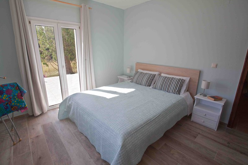 Bedroom with queen size bed and access to the back terrace.
