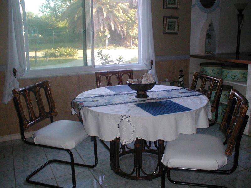 4 cadeiras na área de jantar e uma mesa não retratada. Janelas à prova de furacões