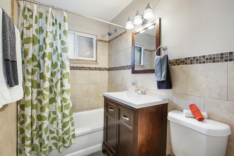 Recién renovado baño completo con combinación de bañera / ducha.