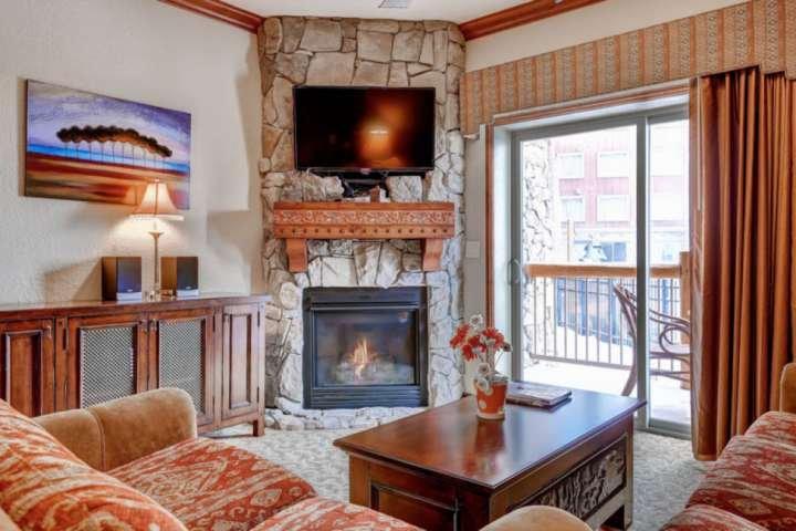 Salon avec cheminée en pierre du sol au plafond, grand téléviseur haute définition à écran plat et balcon privé / espace extérieur.