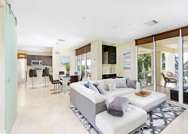 Living room, kitchen and outdoor patio all overlooking the pool