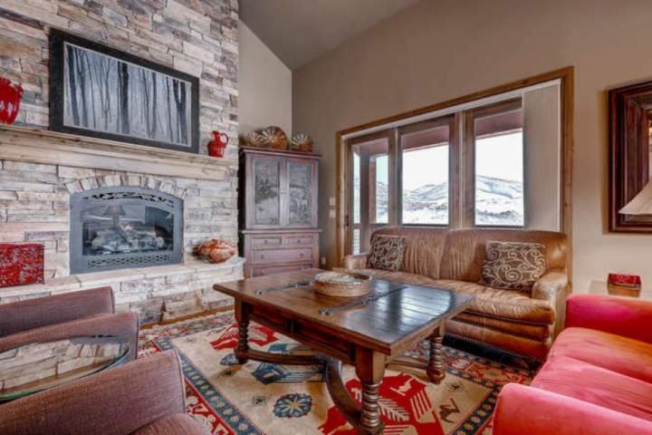 Living room with stone fireplace,HDTV with Satellite TV, WiFi and private balcony overlooking the Wasatch Mountains.