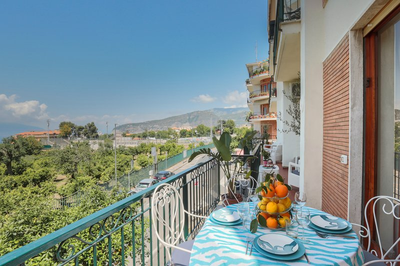 Terraza con vista al mar, muebles de exterior y comedor.