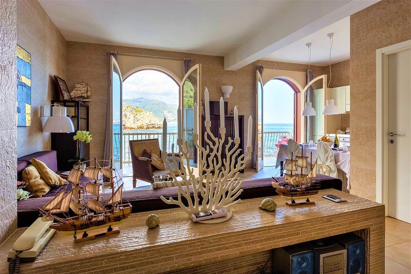 Living room with panoramic doors that open on the terrace with sea view