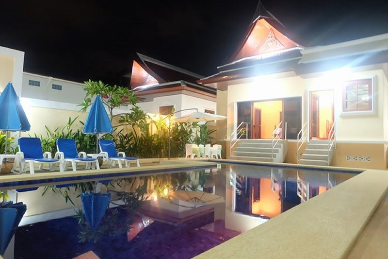 Rear of villa pool area with six lounge chairs so you can put your feet up and table and six seats