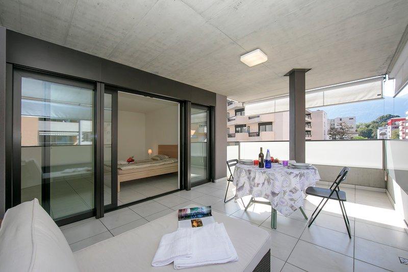 Terrazza arredata con un moderno lettino e un set da pranzo all'aperto