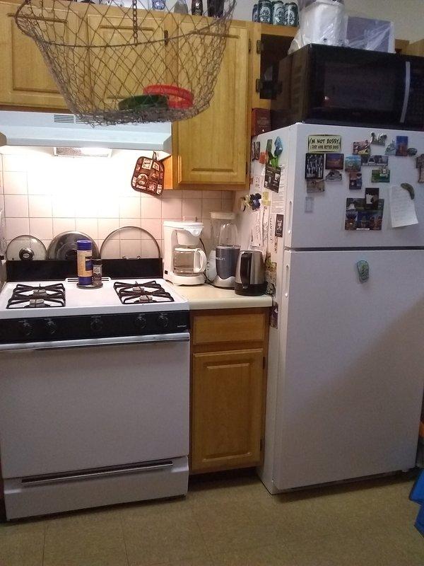 Refrigerador de la cocina, microondas en la parte superior. Cafetera, Tetera, Licuadora Nutribullet, Estufa, Horno Tostador.