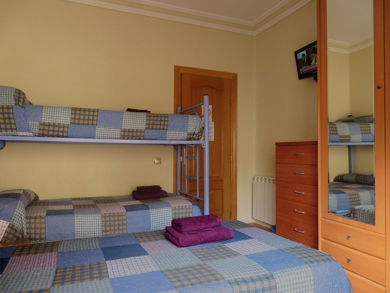 Room with bunk bed + single bed. TV