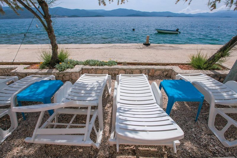 Villa Vedran beachfront apartment C, private large terrace sunbeds best position, holiday rental in Komarna