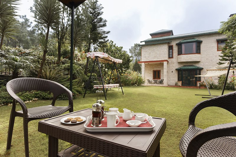 Have a tea in the expansive garden attached to this Vacation Home in Kasauli