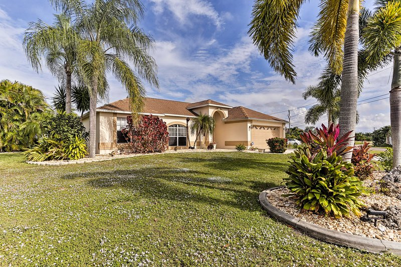 Lofty palm trees and tropical gardens frame this beautiful Cape Coral home.