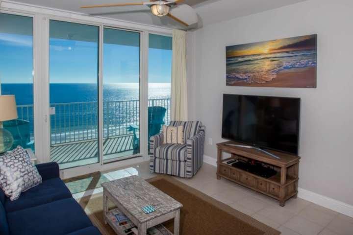 """Sala de estar con azulejos con reproductor de TV / BluRay de 60 """"y acceso al patio frente al golfo"""