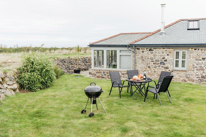 Zone de jardin avec barbecue et table et chaises.