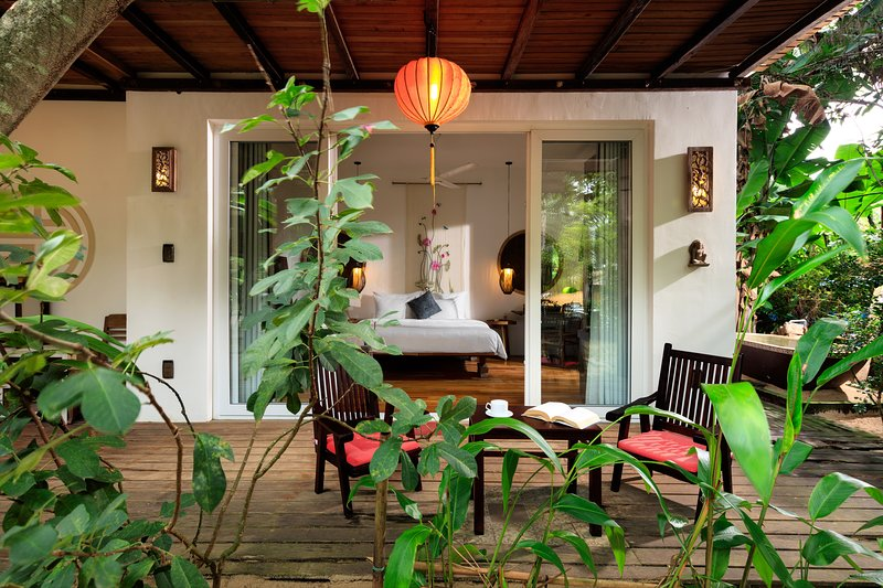 The villa is surrounded by lush tropical garden and pine trees.