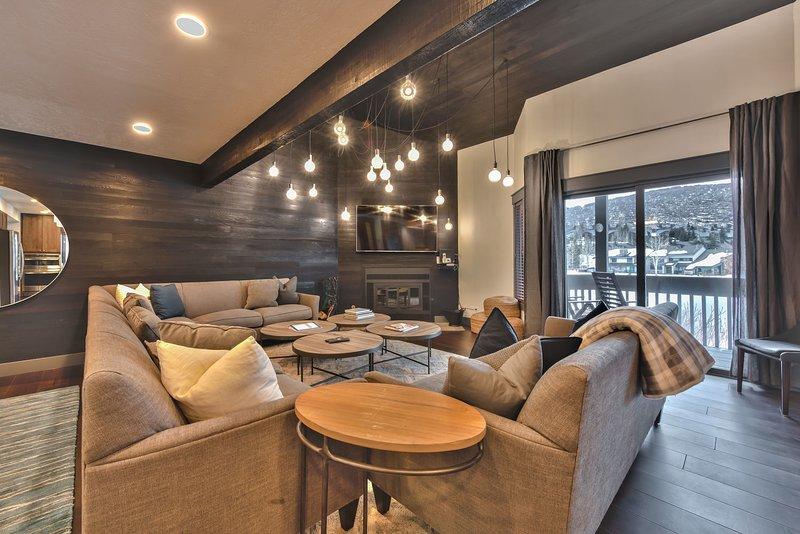 Sala de estar con muebles contemporáneos de montaña, chimenea de madera, TV y balcón privado con vistas al lago y la montaña