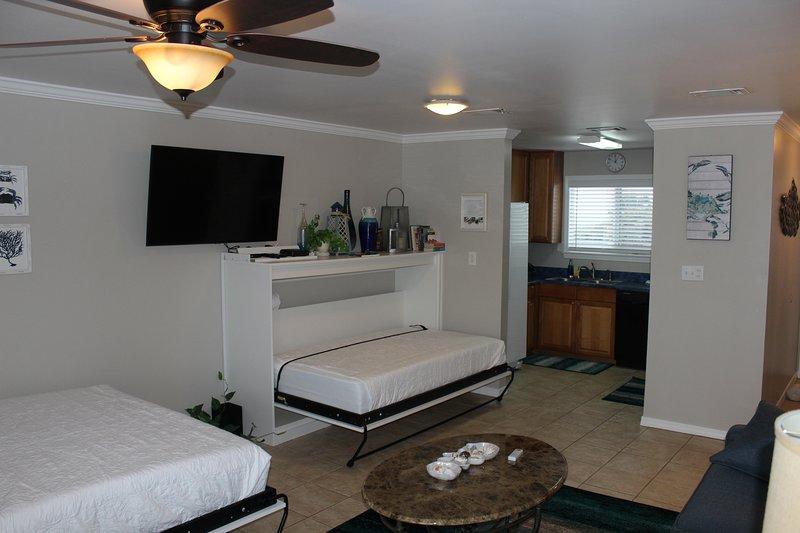 Sala de estar tiene 2 camas Murphy y un sofá cama