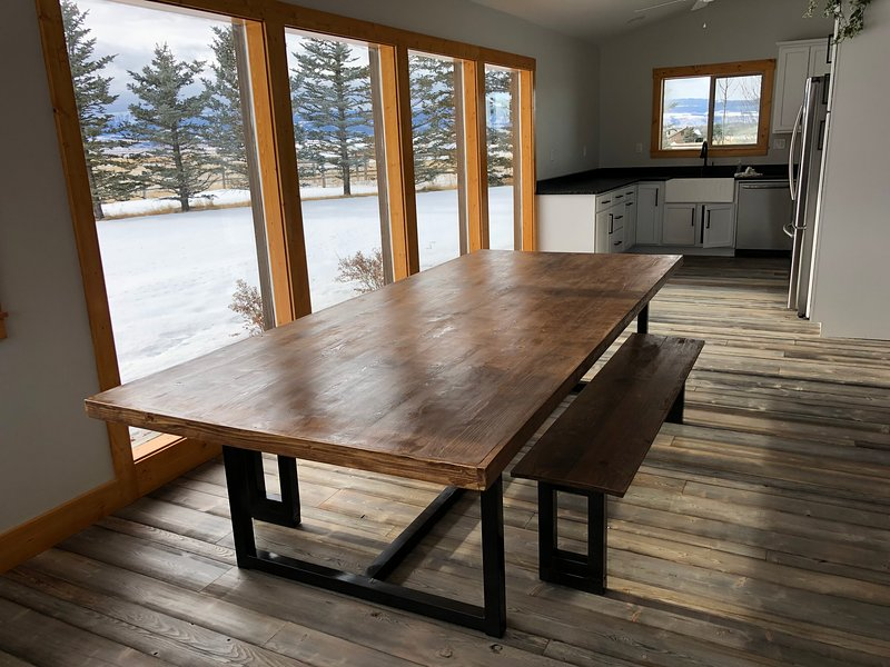 The dining area provides an extra large table with gorgeous views of tall pines.