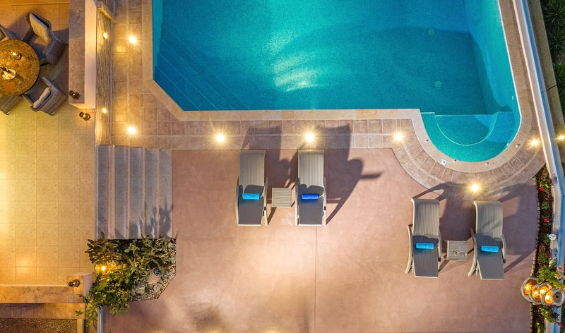 Swimmingpool und Sitzgelegenheiten neben dem Pool