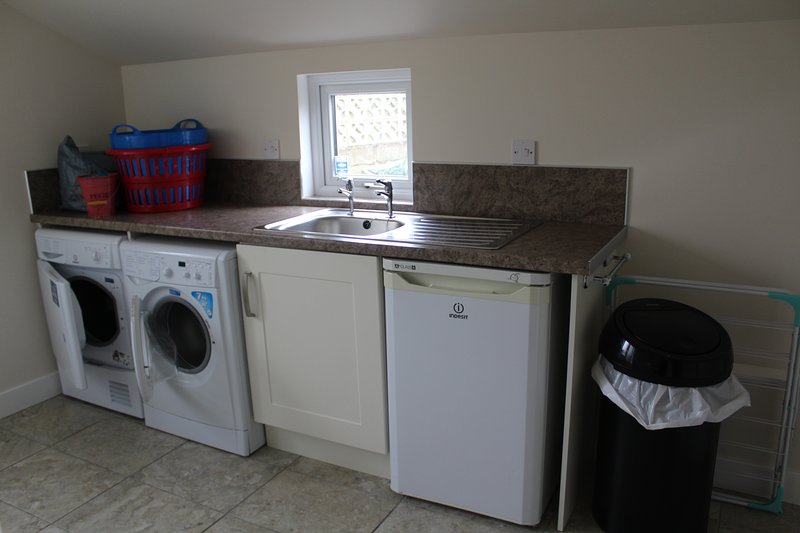 Utility room showing washer, drier and freezer.