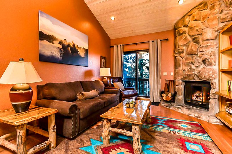 Cozy and tasteful living room, bordering National Forest. Alpine ceiling.  Granite fireplace.