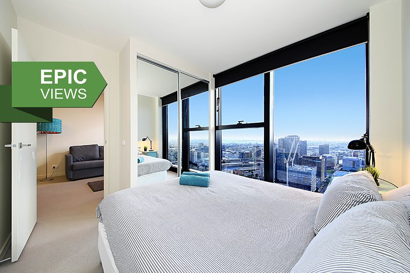 Una camera da letto con un letto matrimoniale, cuscini in peluche e amp; una vista da morire.