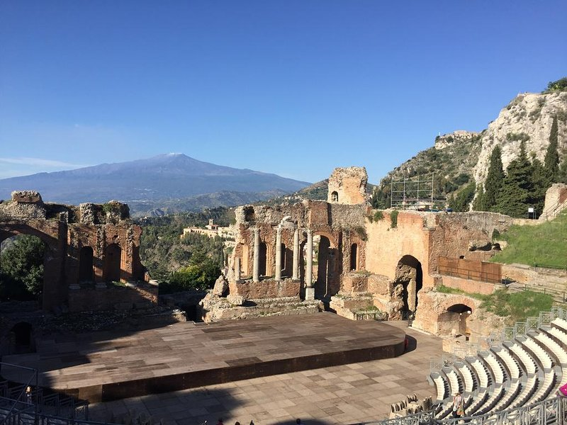 Greek Roman Theater carved into the rock with a breathtaking view of the bay of Giardini Naxos and Etna