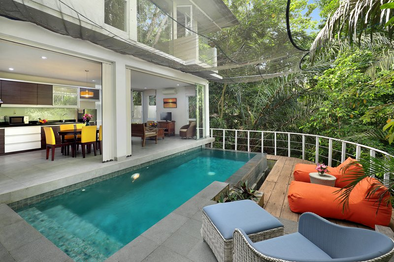 The pool deck overlooks lush forest and a waterfall.
