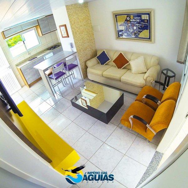 Sala de estar com TV na sala e cozinha