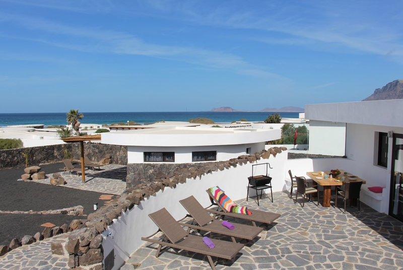 Grande terrazza solarium con lettini, barbecue, doccia esterna, zona pranzo e idromassaggio con vista sull'oceano