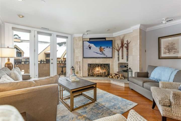 The living room includes comfortable modern furnishings, wood burning fireplace, flat screen TV and deck access.