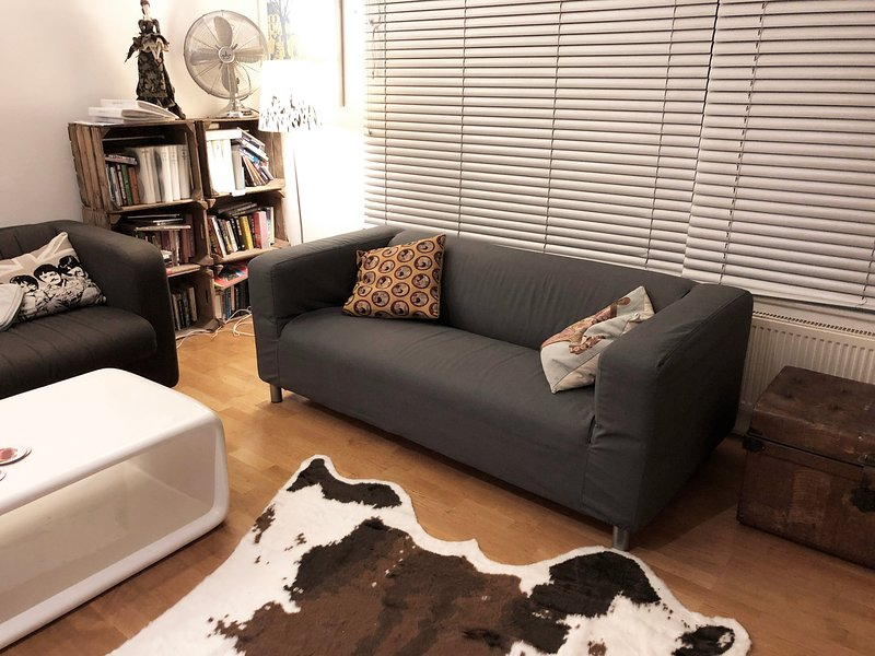The living room sofa has a stylish grey cover
