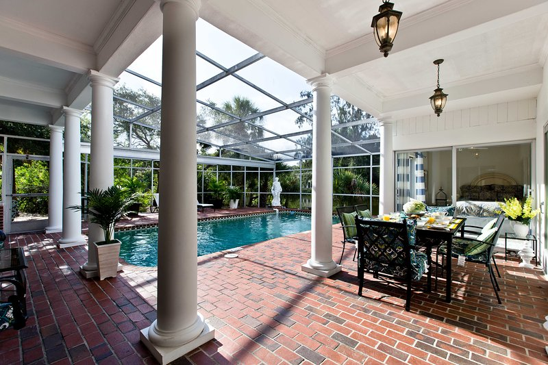 Large retractable glass doors leading to screened in pool and lanai providing both sun and shade