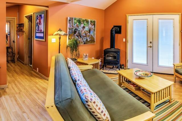 The spacious guest house features a great room with a gas 'wood' stove, smart tv, and a futon for extra guests. (sleeps four total).