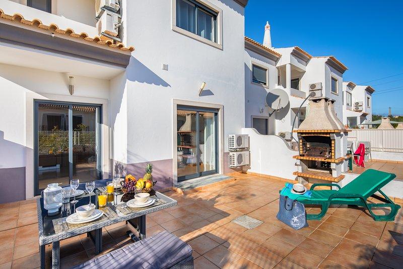 Terraza privada amueblada con mesa y silla con barbacoa.