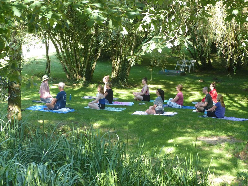 Anyone for yoga? Group class in shade by the stream.