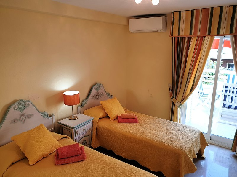 The apartment's third bedroom, with two single beds and its own AC unit.