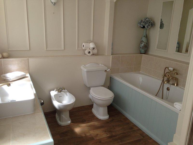 De moderne eigen badkamer is voorzien van een bad, een bidet en een inloopdouche.