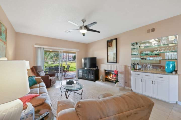 Comfortable open living room has ample seating, a large Smart TV with Cable, fireplace, ceiling fan, and wet bar.