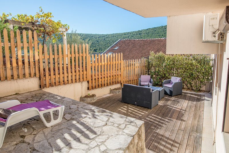 Large back terrace, suitable for sunbathing and alfresco meals, provides privacy and shade
