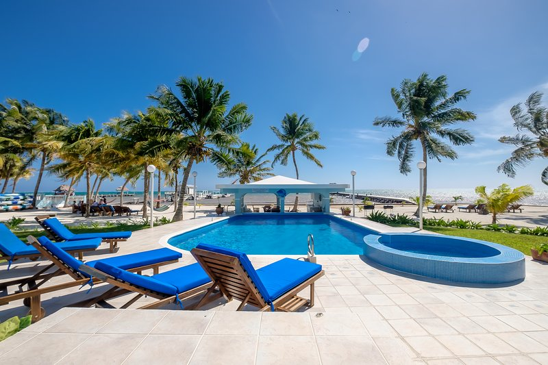 View of sparkling pool,  comfy lounge chairs, waving palms, covered gazebo,beach and dock beyond!