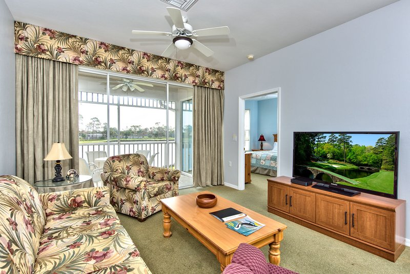 Living Room with Flat Screen TV, Fan, and Entrance to Lanai Area with Lake and Golf Views!