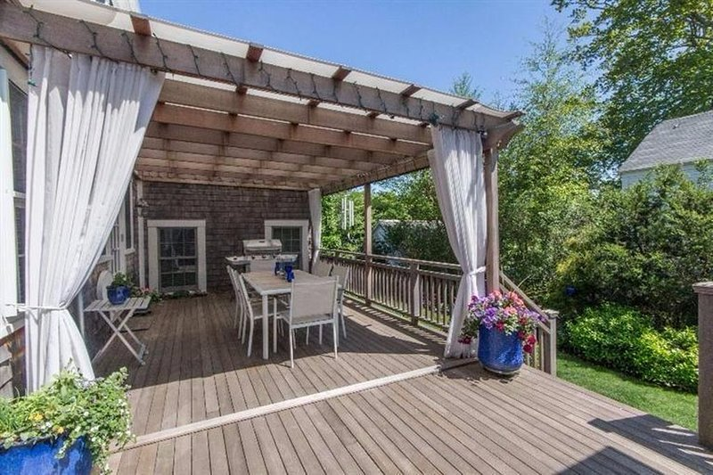 Covered deck with seating for 8 overlooking private landscaped yard